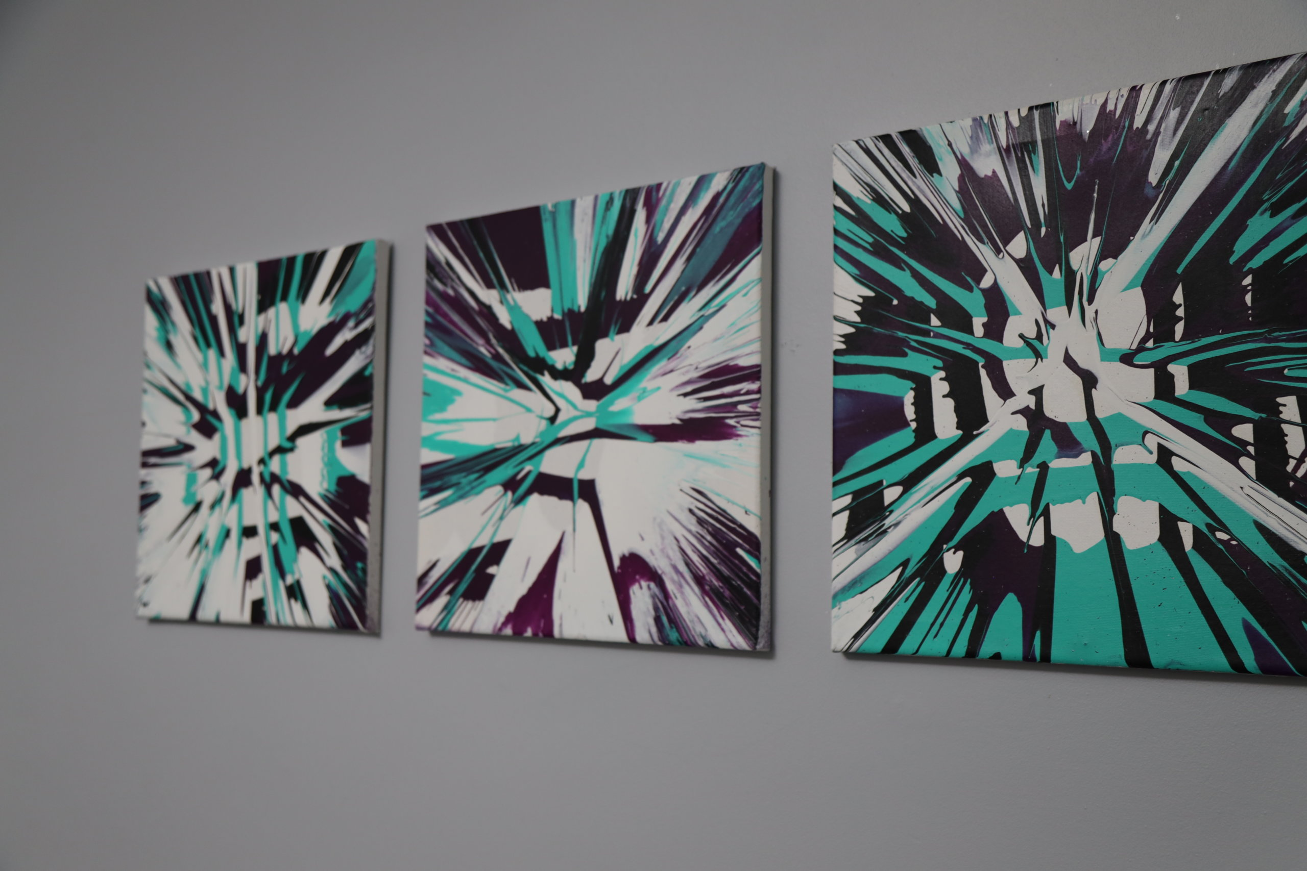 three completed spin art canvases hanging