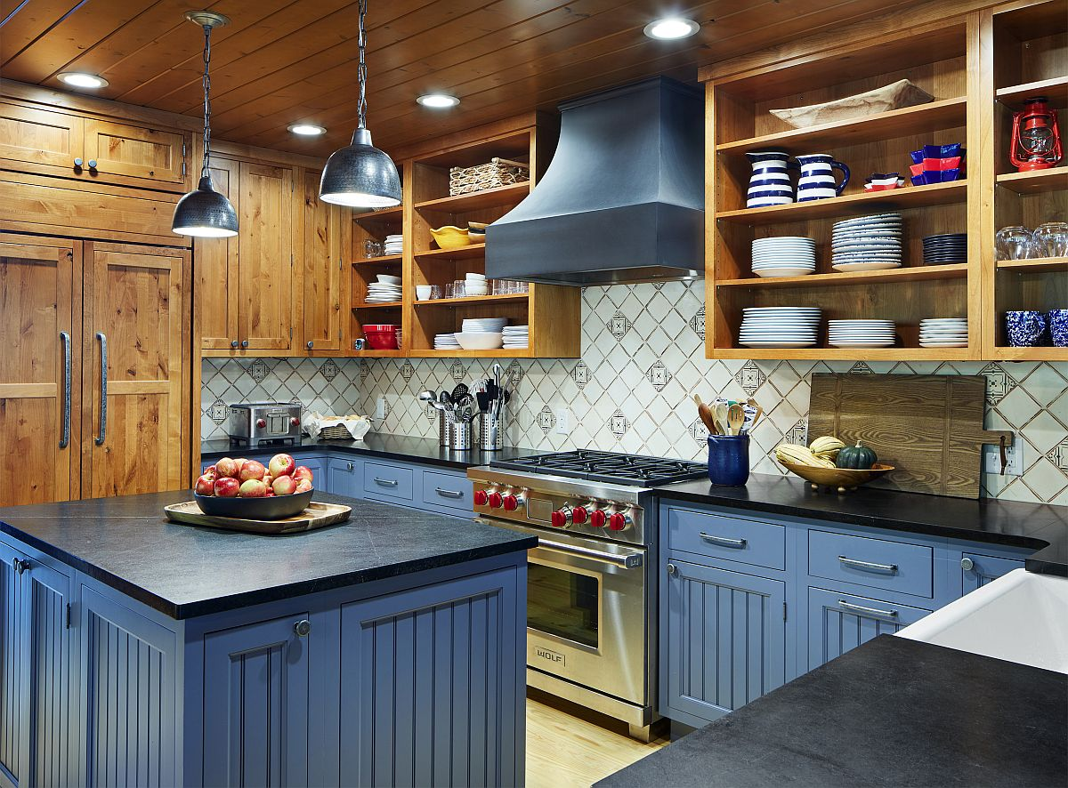 Blue cabinets and island couped with wooden shelves and cabinets in the functional rustic kitchen