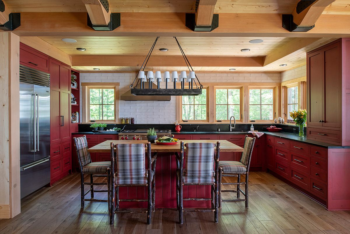 Brilliant red cabinets in wood and chairs around the island with pattern make an impact in this kitchen