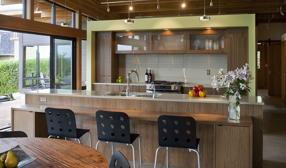 Contemporary kitchen with a wooden island and breakfast bar along with a hint of light green thrown into the mix