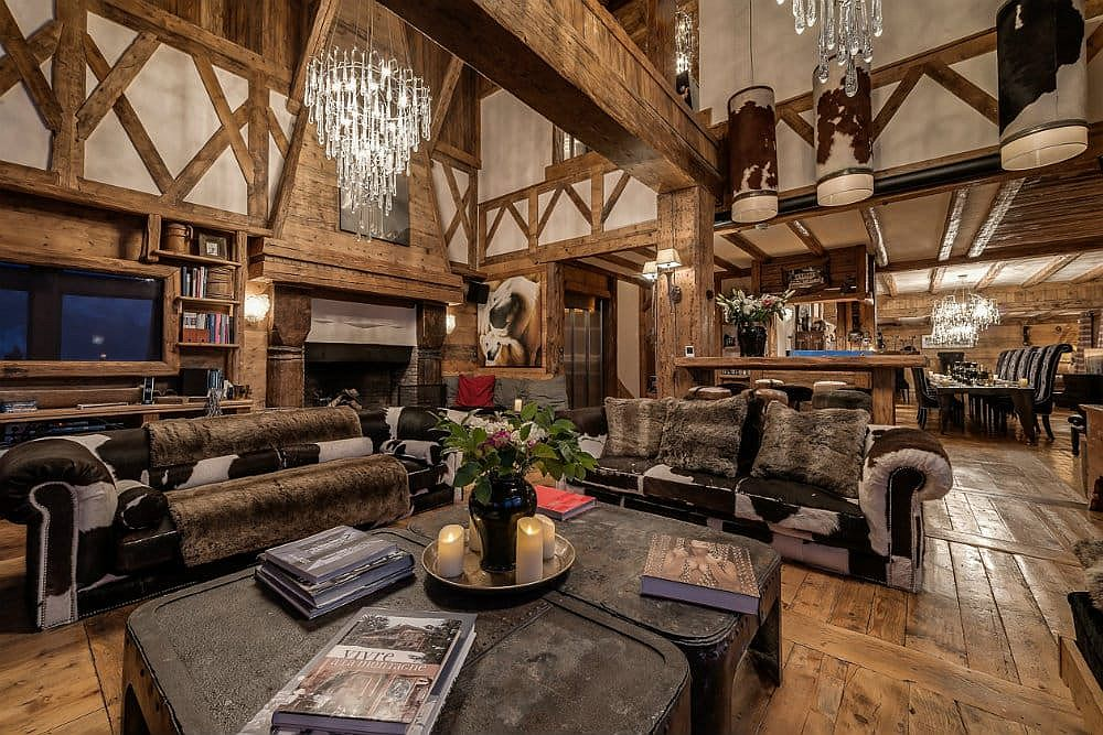 Cozy couches, cowhide rugs and lovely chandeliers create a sense of luxury inside this chalet living room