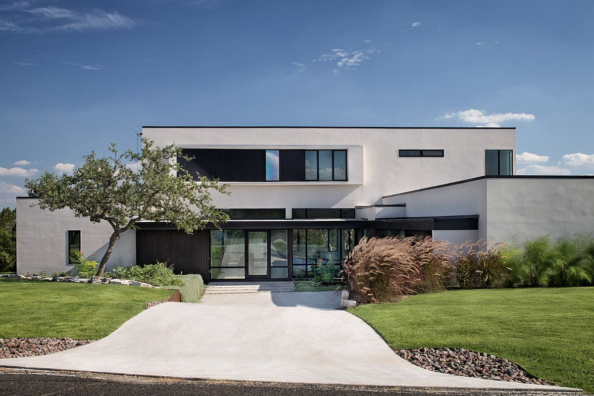 Dark and dashing framed entry of the home in white and glass is a showstopper