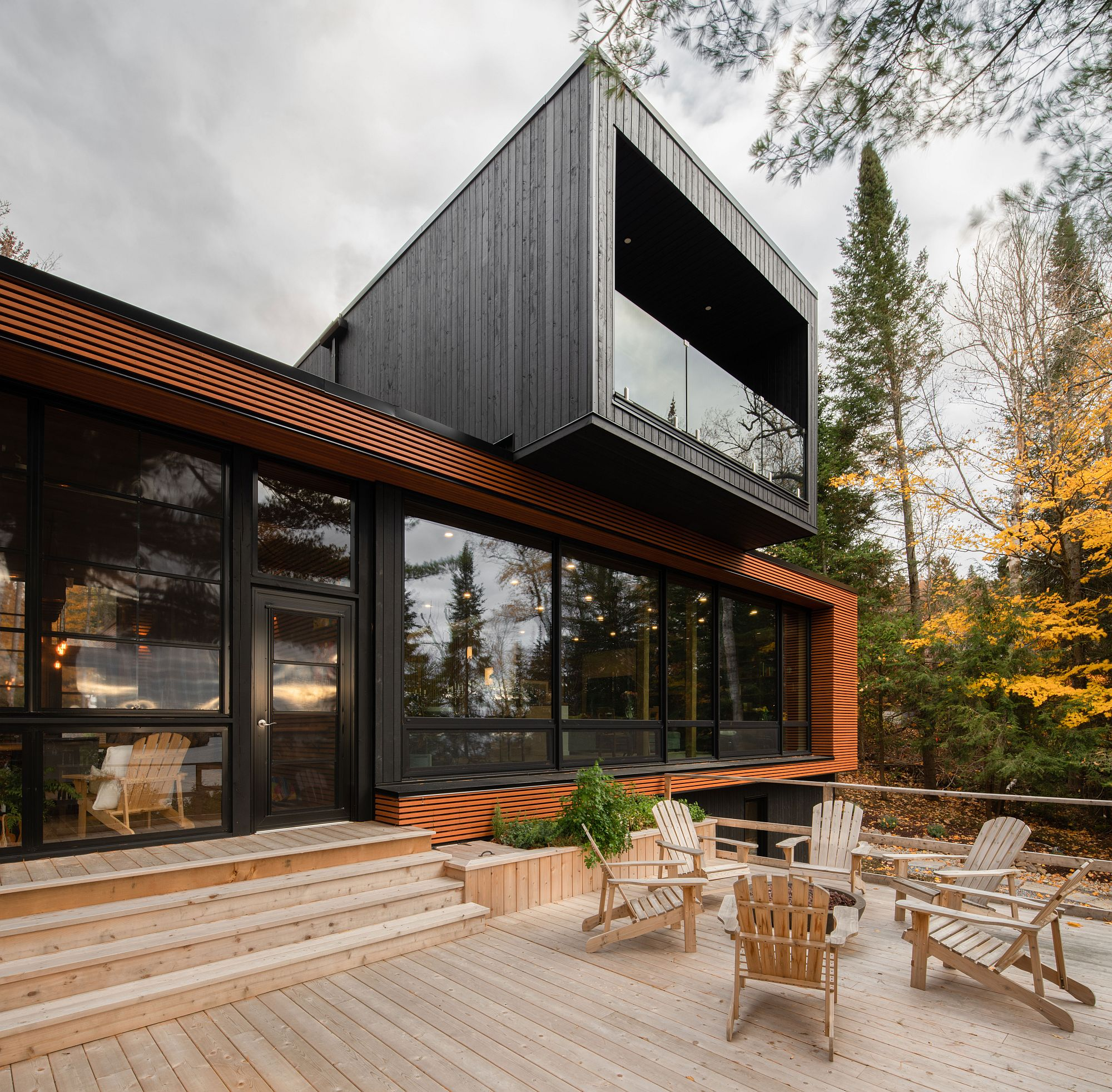Dark, cantilevered upper level of the house stands in contrast to the lower level with natural finish