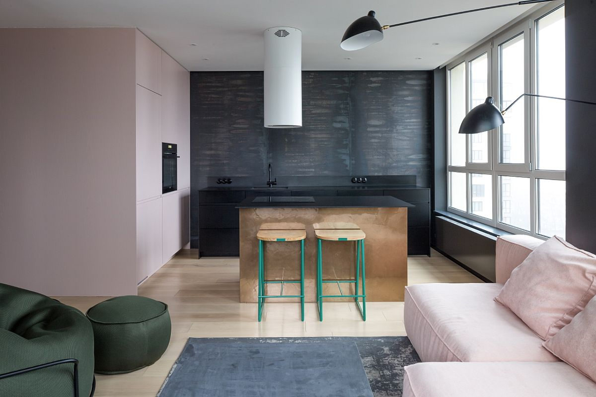 Dark kitchen in backdrop with custom brass island and colorful bar stools
