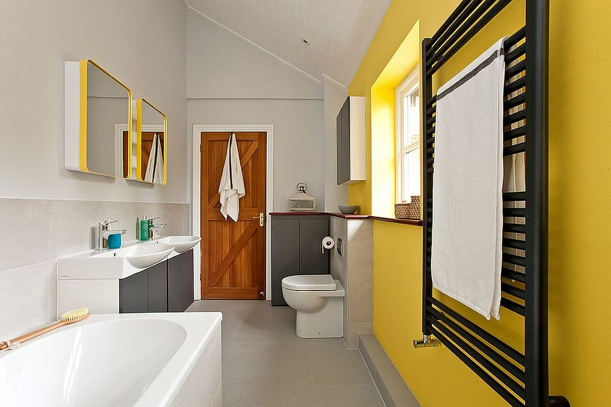 Dashing accent wall in yellow for the contemporary bathroom in yellow and gray