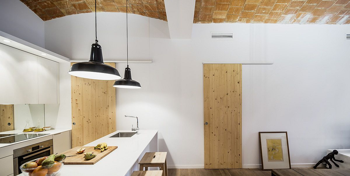 Dashing and bright kitchen and dining space of the home in wood and white with ceramic-tiled ceiling