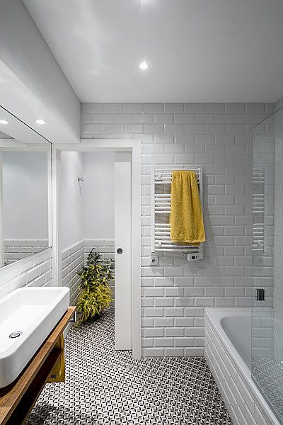 Delightful, light-filled bathroom in white where the floor tiles usher in pattern