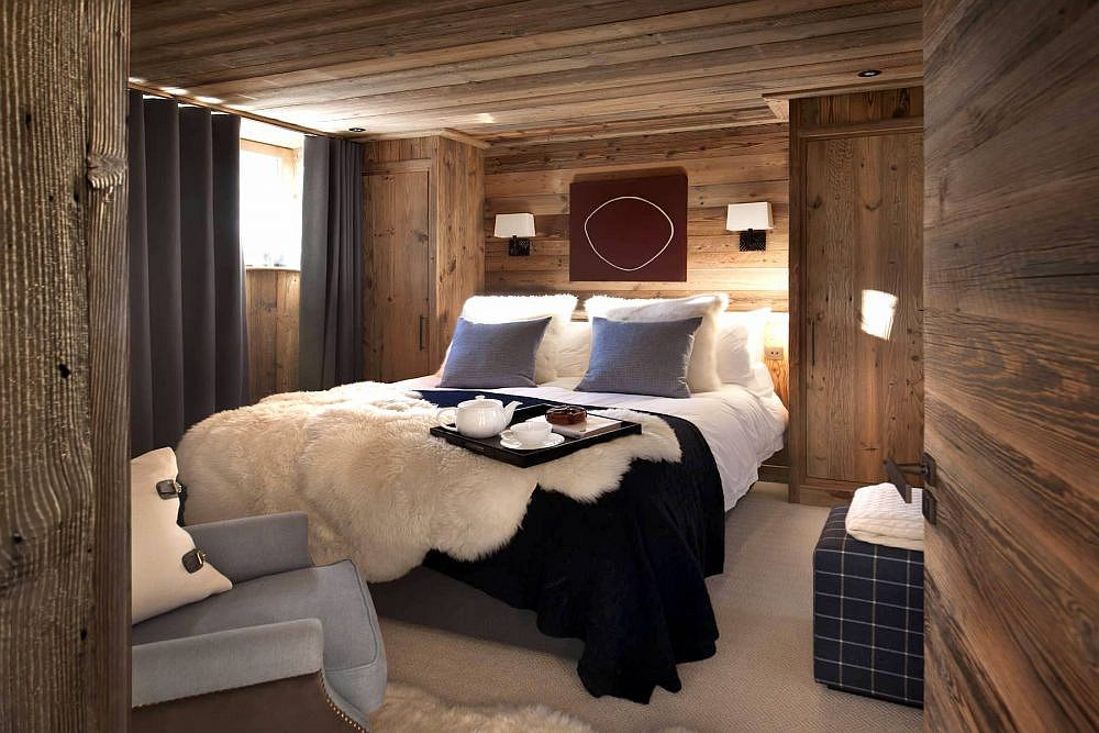 Drapes and pillow colors bring dark bluish-gray to the woodsy cabin-style bedroom