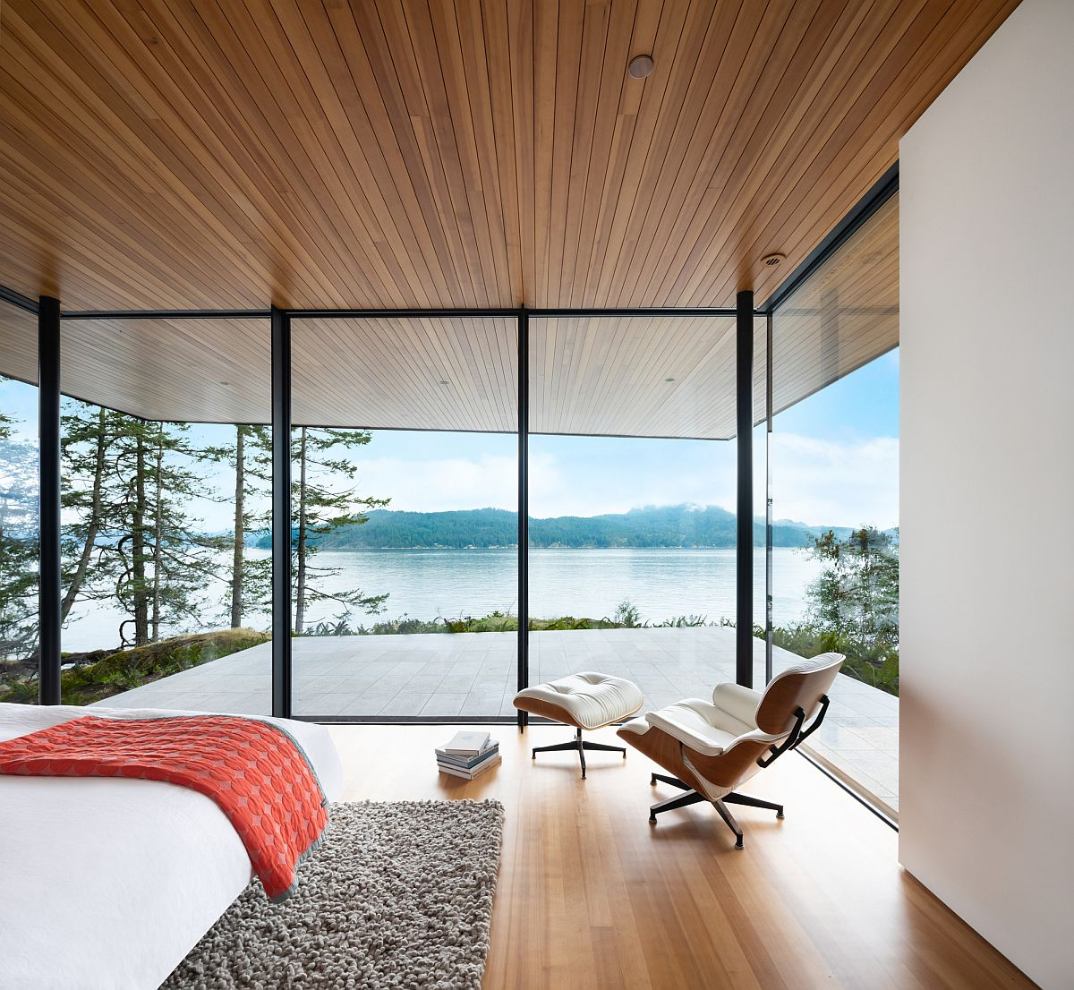 Floor-to-ceiling glass walls open up the bedroom to the stunning ocean view and beyond