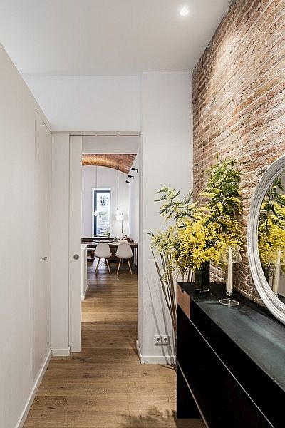 Gorgeously-lit corridor with exposed brick wall leading to the open plan living space