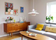 corner of mid century modern living space with carved credenza and low hanging light