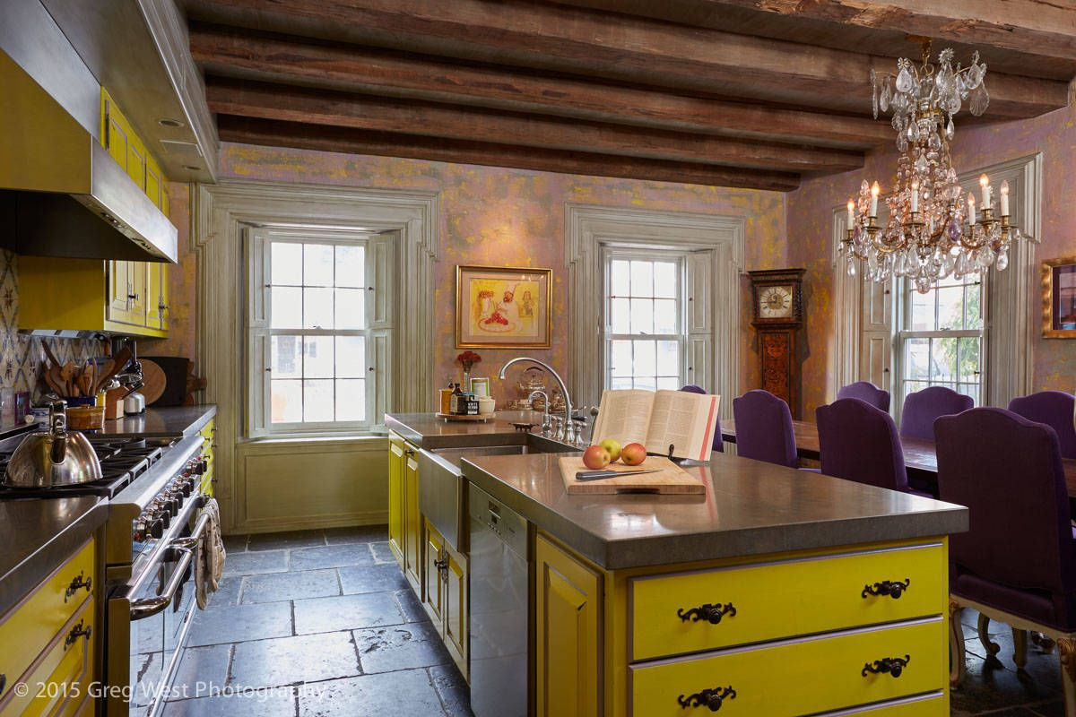Kitchen island and cabinets add brilliant splashes of yellow to this lovely rustic kitchen