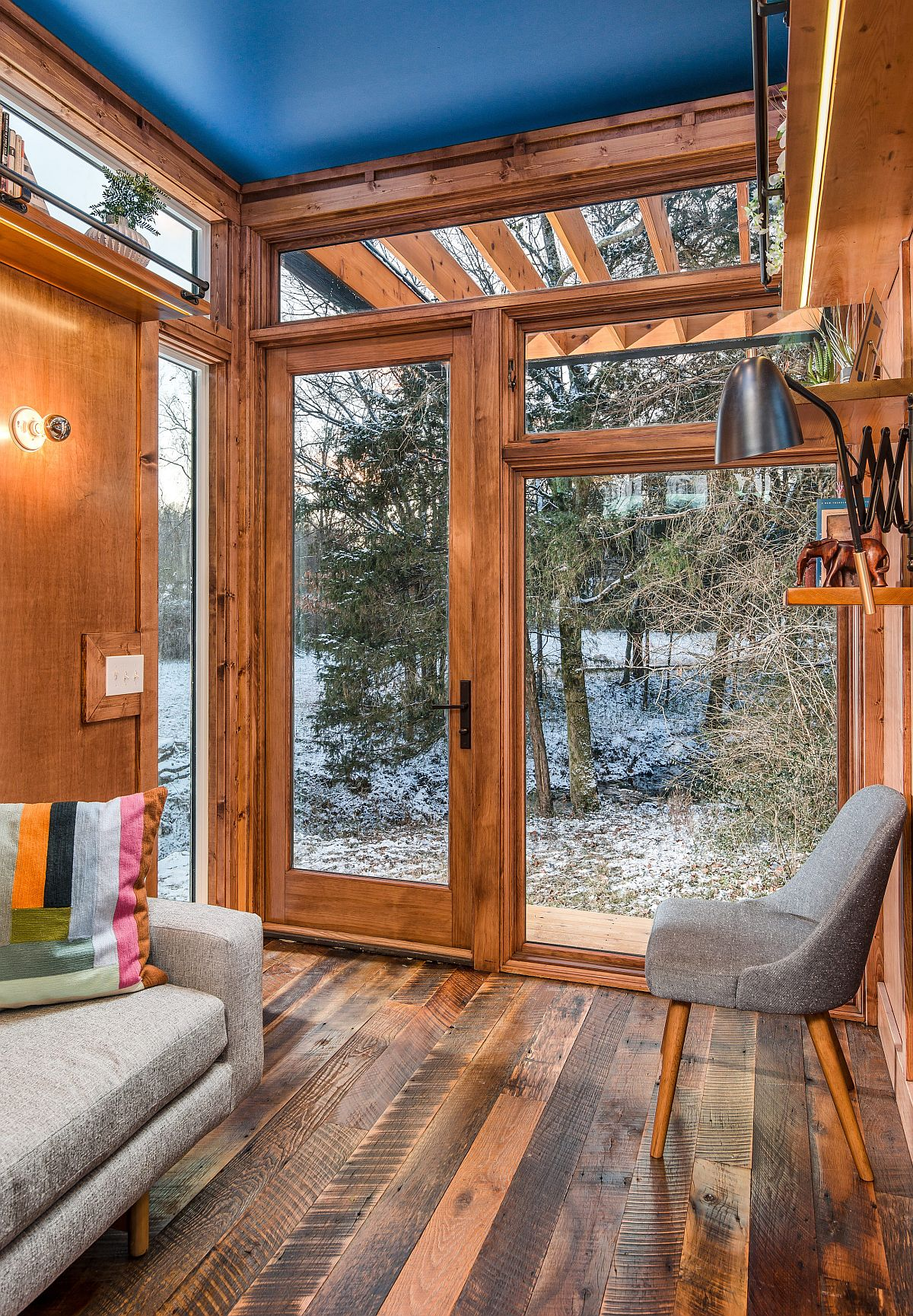Large glass doors and windows bring light into the small cabin