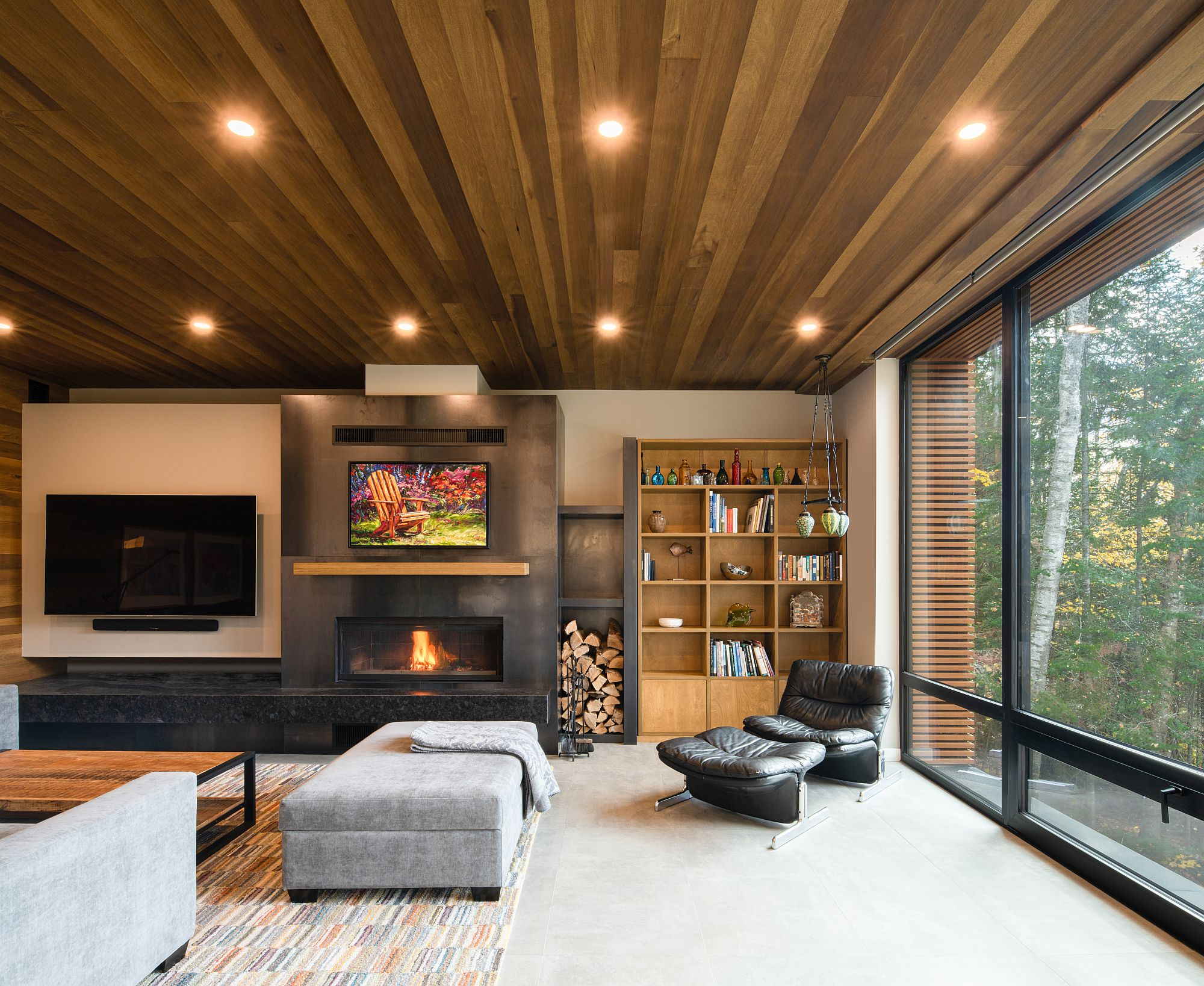 Living area of the house with a smart fireplace, woodsy ceiling and large floor-to-ceiling glass walls that bring the outdoors inside