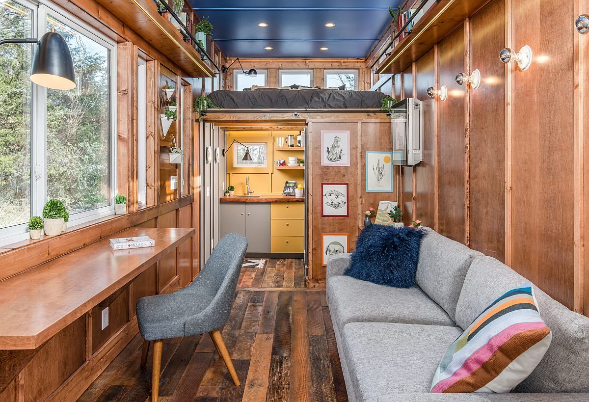 Look at the living and writing space, kitchen and loft sleeping area of the tiny home