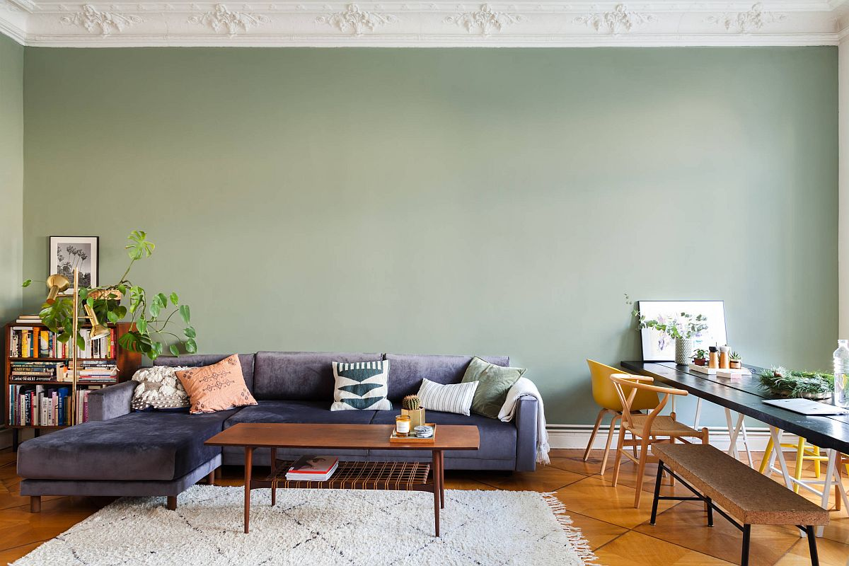 Mint green accent wall for the living room with a dark gray couch