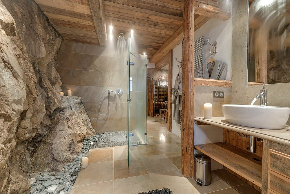 Natural rock becomes a part of the bathroom at this gorgeous alpine chalet
