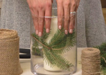 placing evergreen clippings around candle in vase