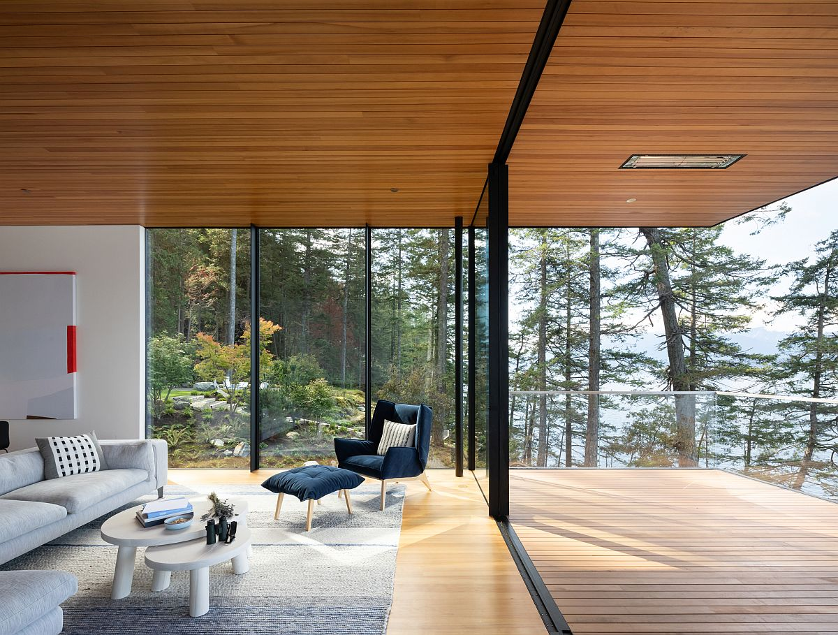Sliding glass doors connect the interior with the natural wooden deck