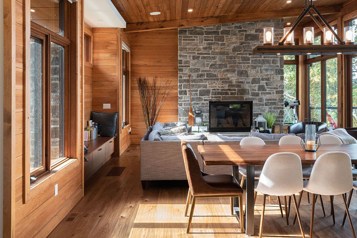 Stone accent wall for the cabin-style living room in wood and glass