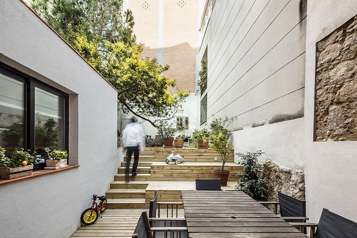 Wooden steps and courtyard lead to the private yard with large tree
