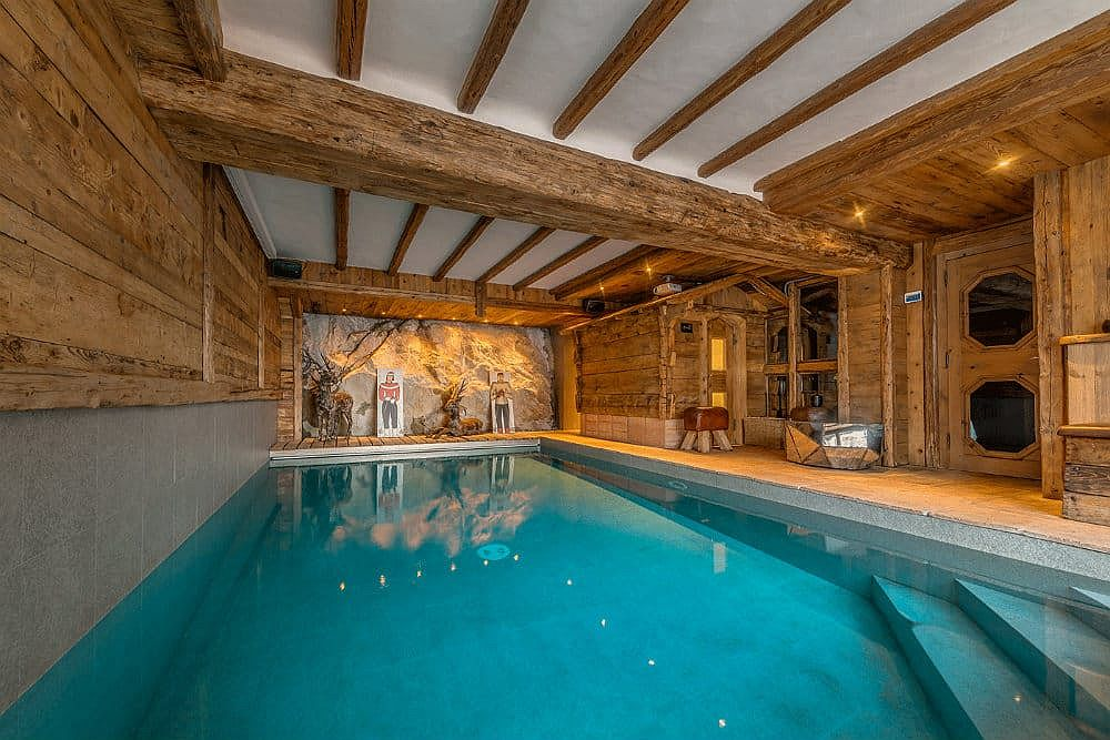 Wooden walls, doors and ceiling beams add warmth to the indoor swimming pool