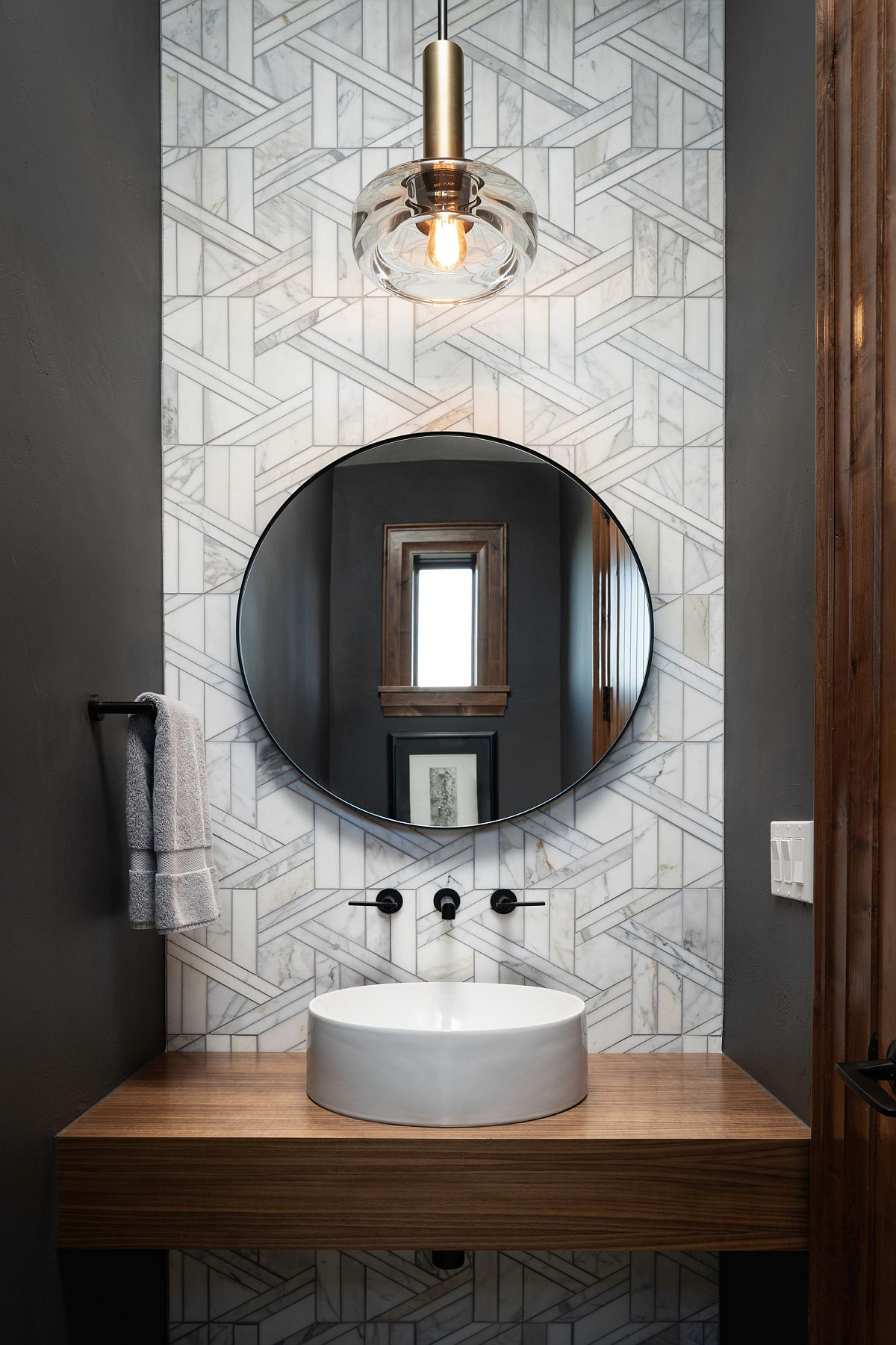 Backdrop with a bit of pattern can bring plenty of contrast to the dark, tiny powder room