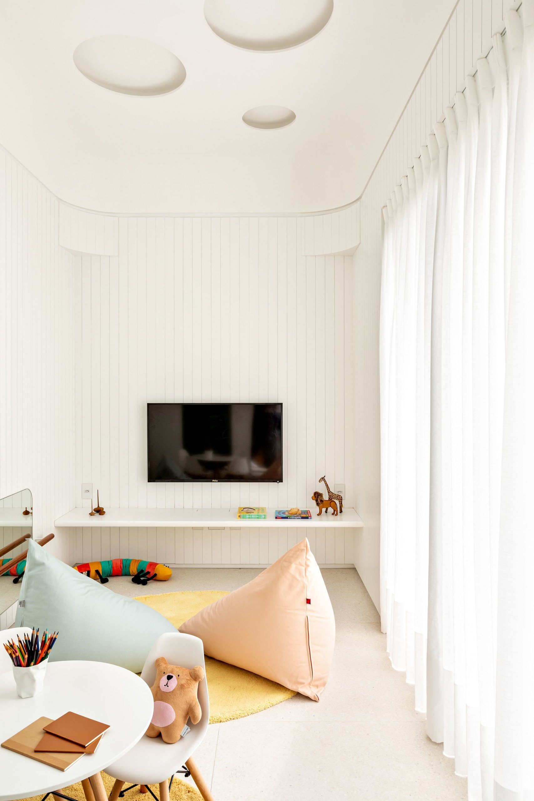 Contemporary kids' play area in white with custom storage units