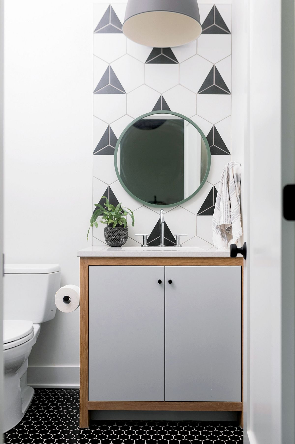 Contemporay powder room in black, white and graywith hexagonal tiles in the backdrop and dark hexagonal floor tiles