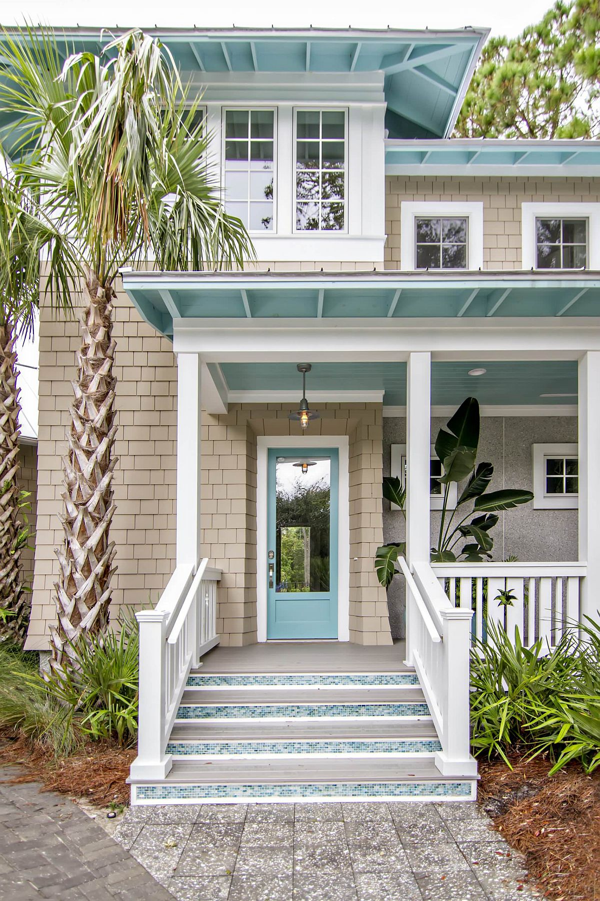 Exquisite pops of light turquoise brighten the street facade of this home in white with a beachy vibe