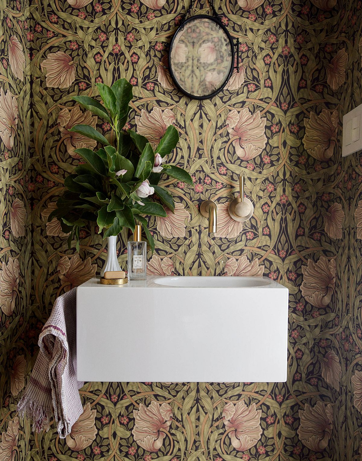 Floral pattern of the wallpaper accentuates the natural appeal of this smart modern powder room