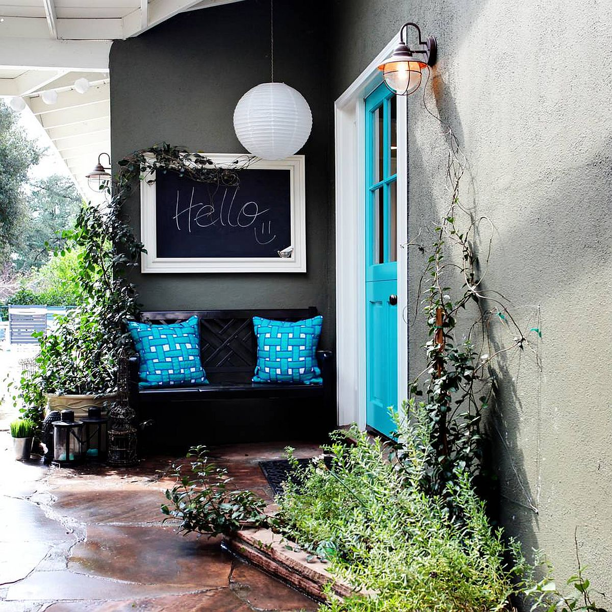 Gorgeous blue door coupled with blue cushions on the bench add color to the gray and white exterior