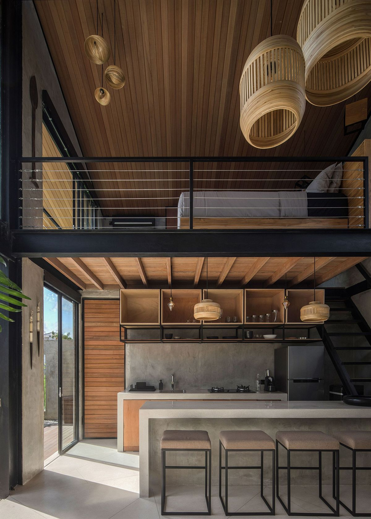 Industrial style home in Indonesia with a loft level bedroom above the kitchen