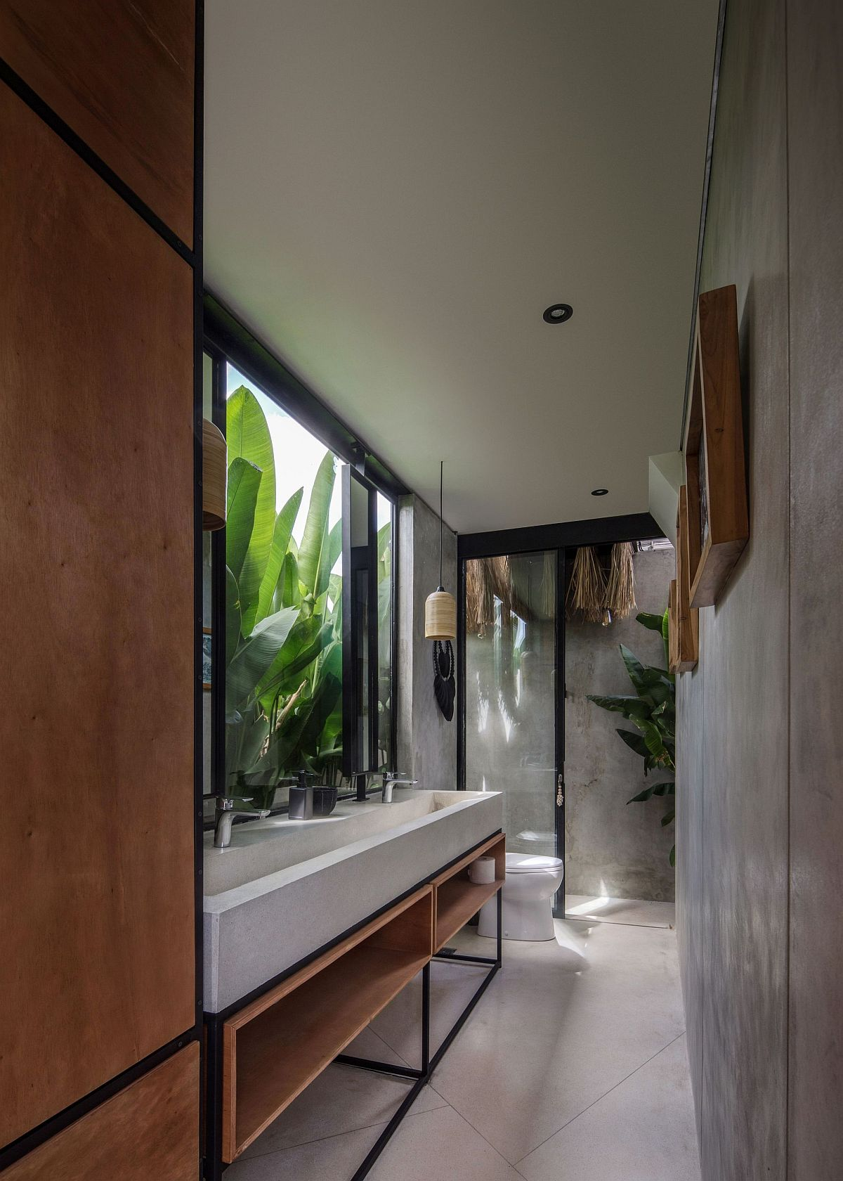 Large banana plants outside become a part ofthe modern minimal bathroom in here