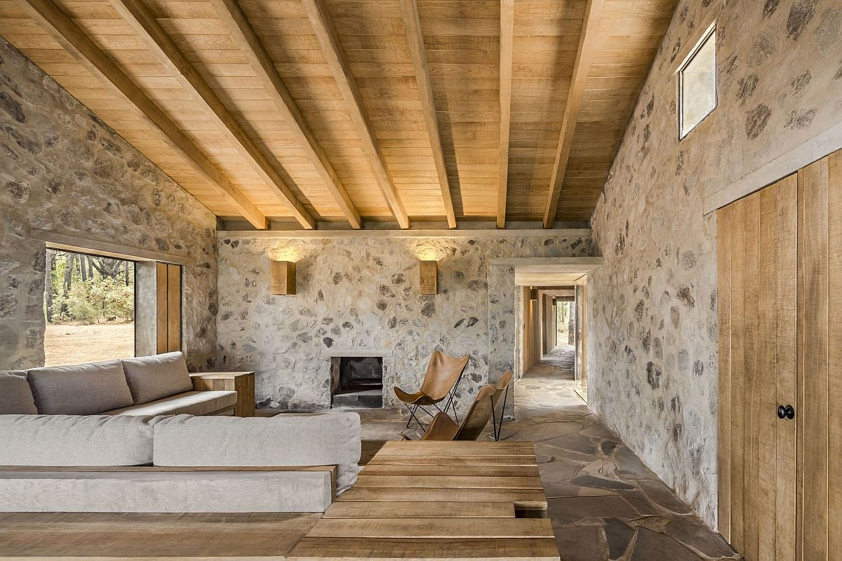 Living area of the cabin with stone walls and a sloped wooden ceiling