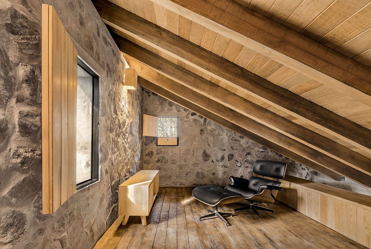 Low and sloping roof of the room leaves little space for the Eames lounger and the small wooden console