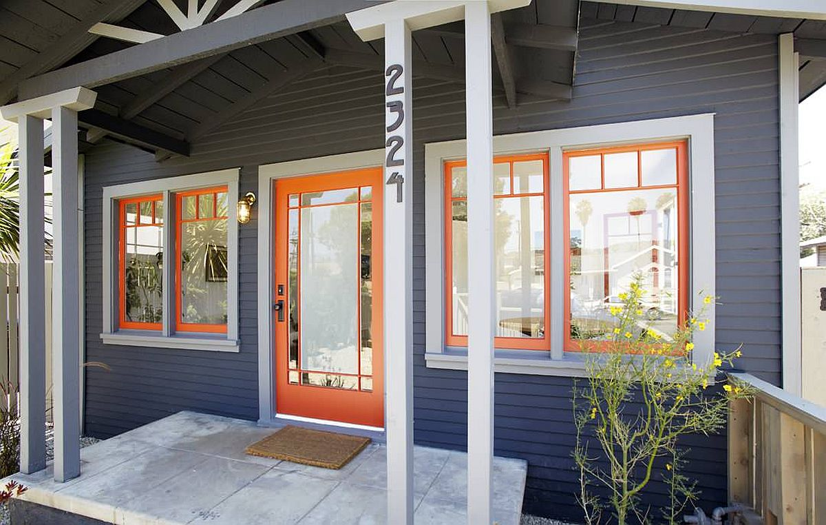 Orange door and window frames bring brightness to this dark gray home exterior