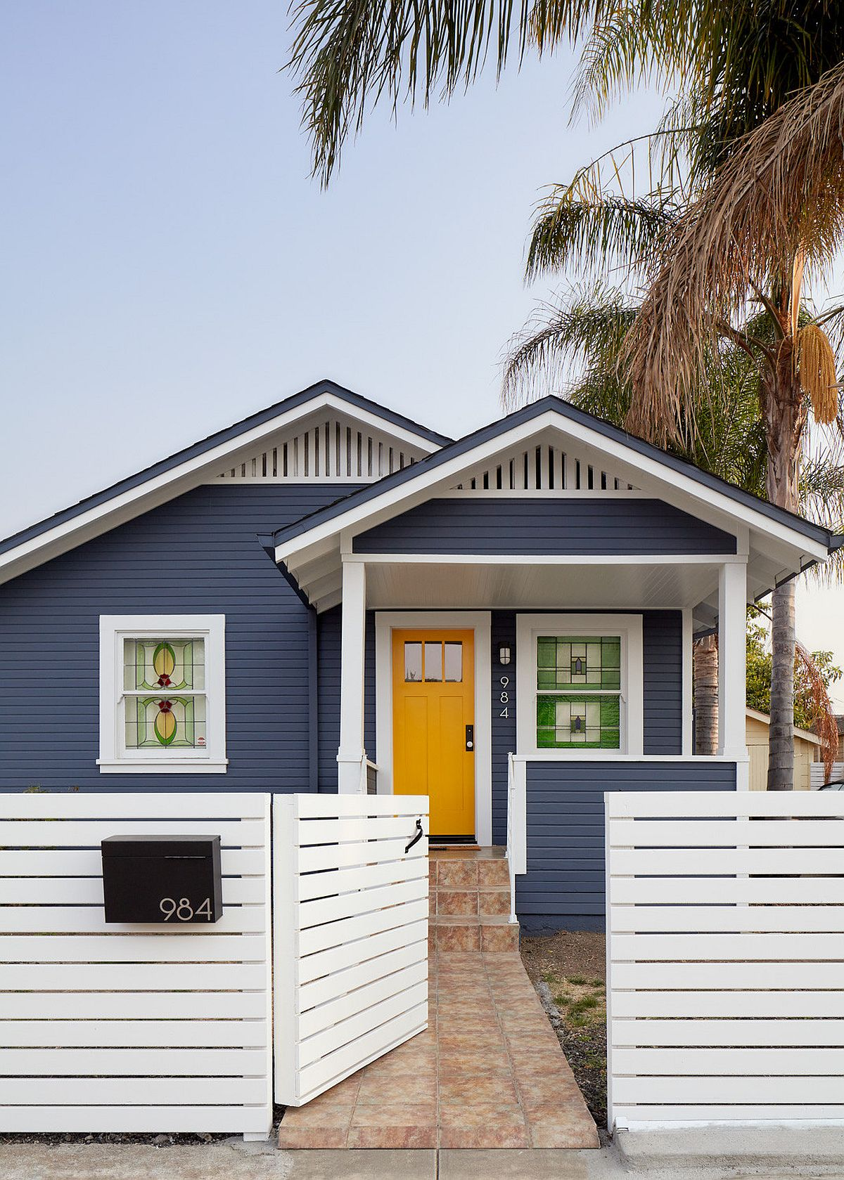 Picture-perfect modern home facade in bluish-gray and white with a dashing and trendy dark yellow door that welcomes you gleefully