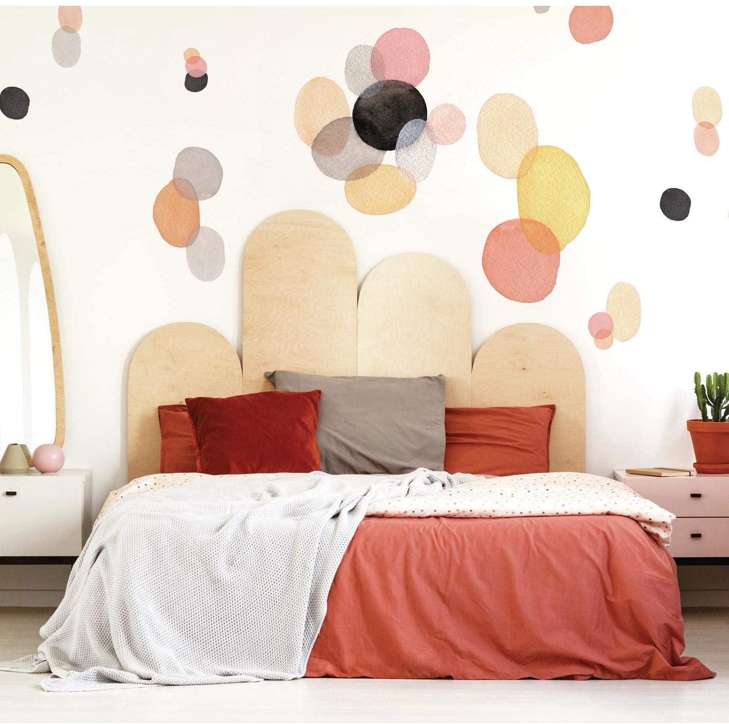 Red bed with pillows and geometric pattern in wall