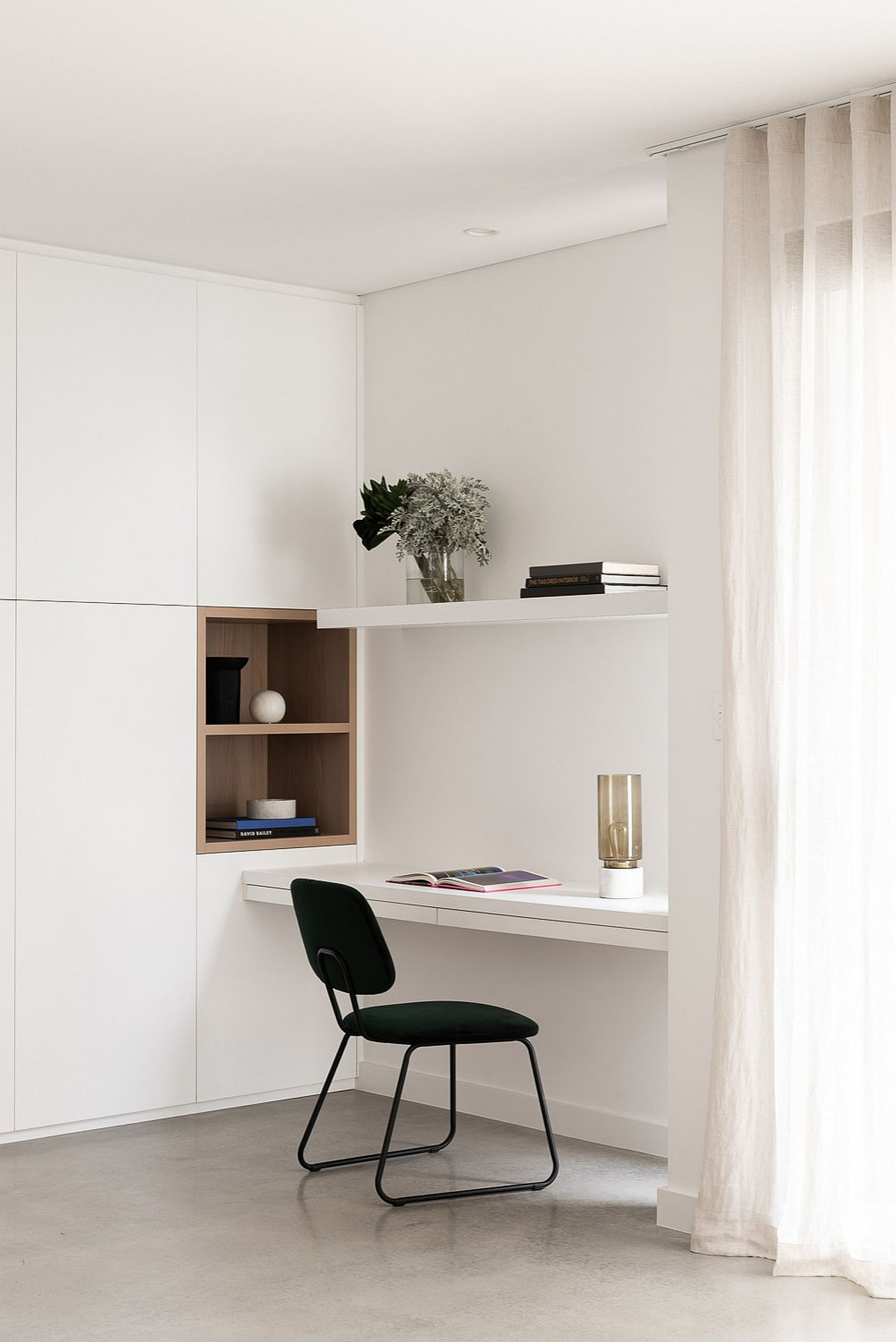 Tiny and minimal workspace in white with a dark chair that adds contrast