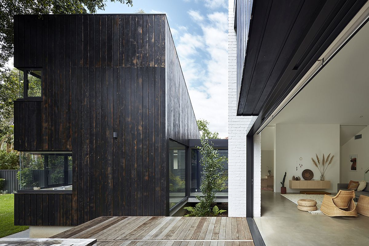 Transition between dark, charred wood finishes and lighter indoor elements is seamless