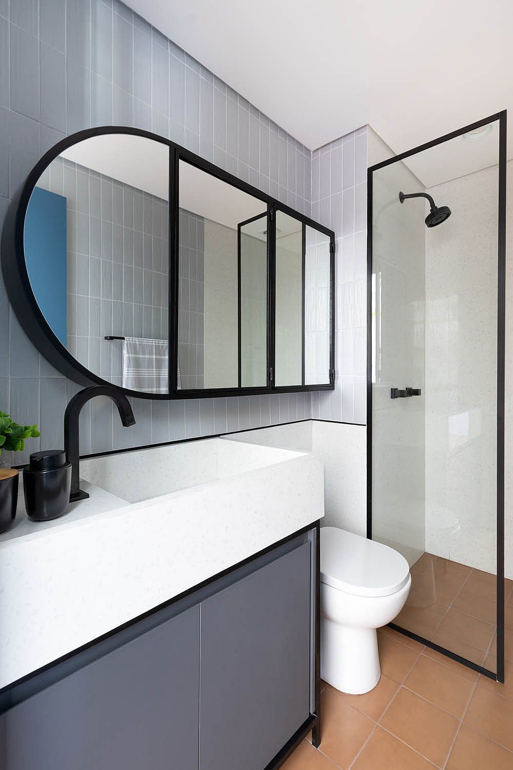 Bathroom in bluish-gray and white along with stylish contemporary mirror