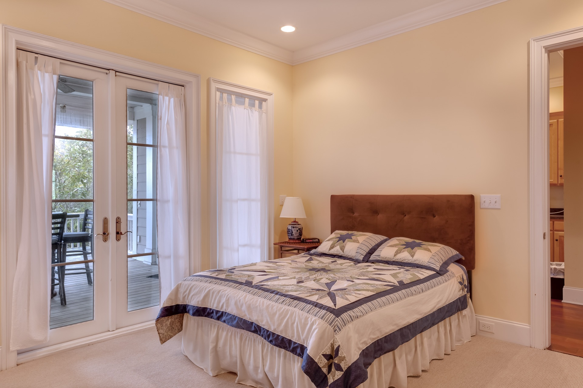 Beige bedroom with large bed and closed doors to the patio