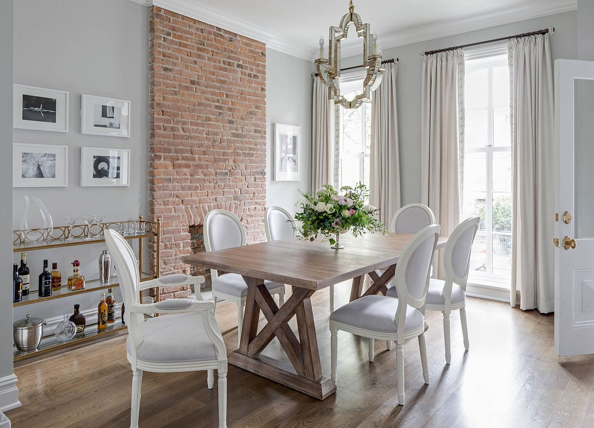Brick wall section steals the spotlight in this contemporary dining space in neural hues