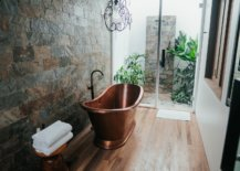 Bronze tub with black faucet and two white folded towels
