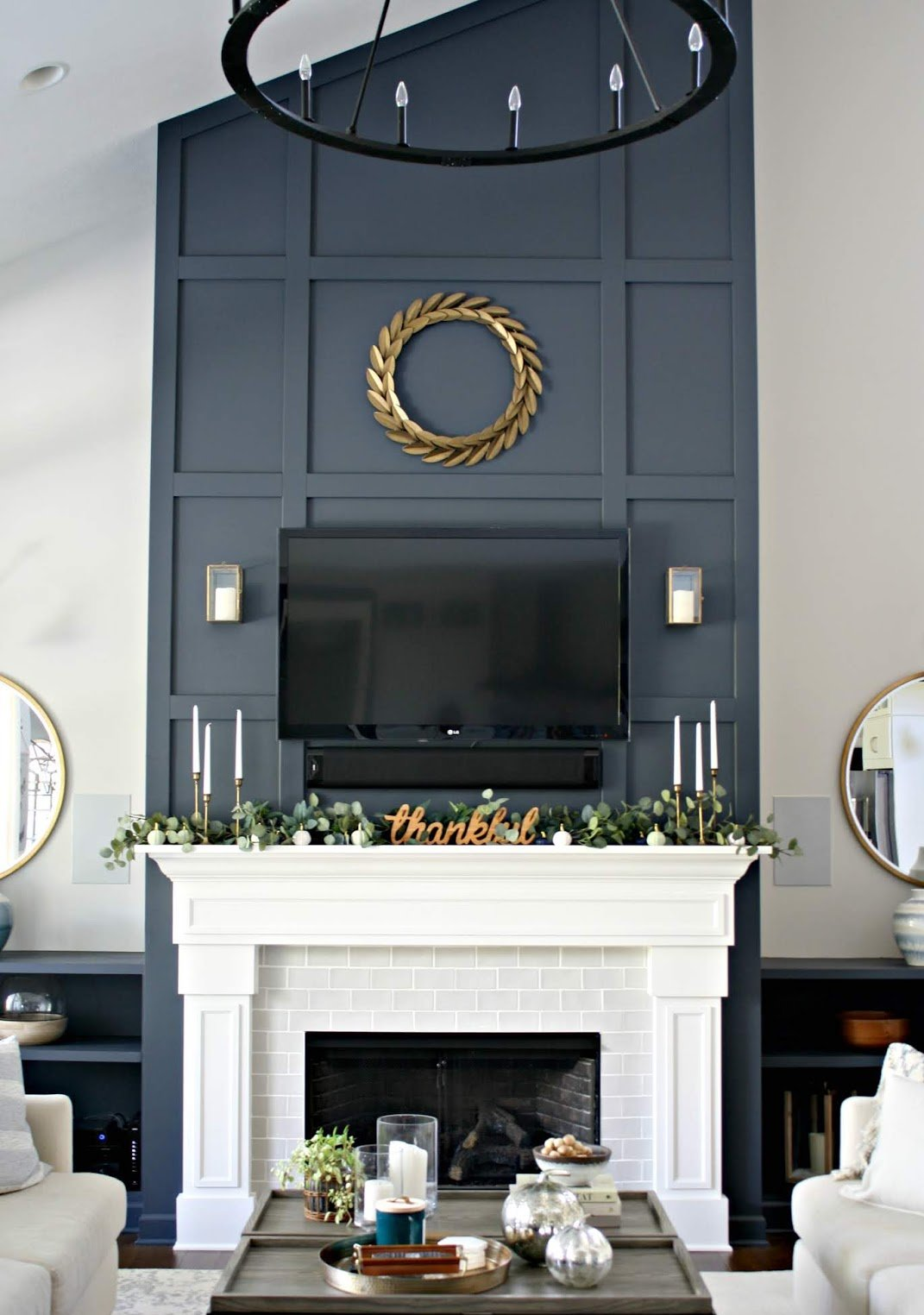 Candles and plants on top of white mantel and fireplace