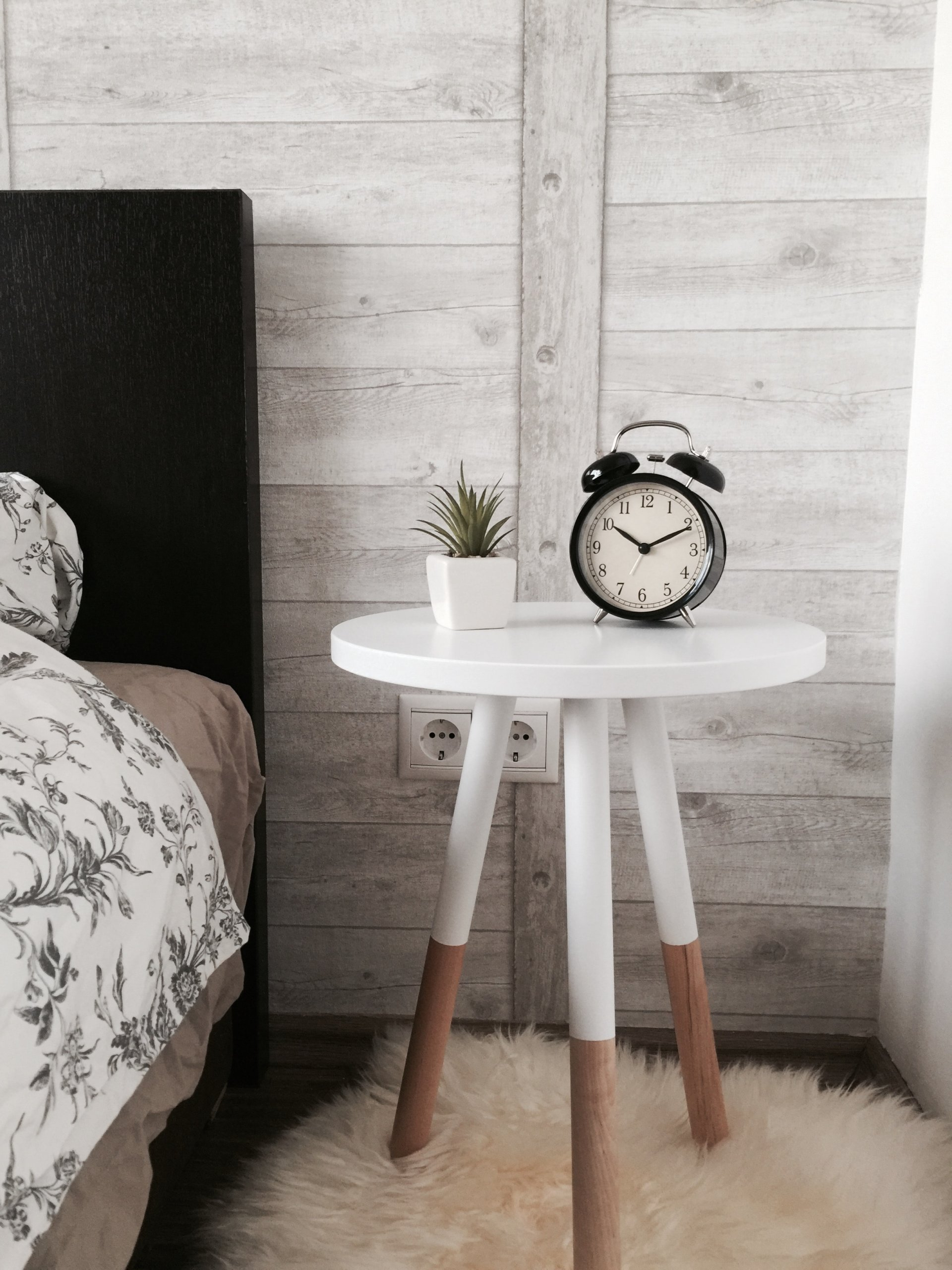 Clock and plant on a white bedside table with three legs