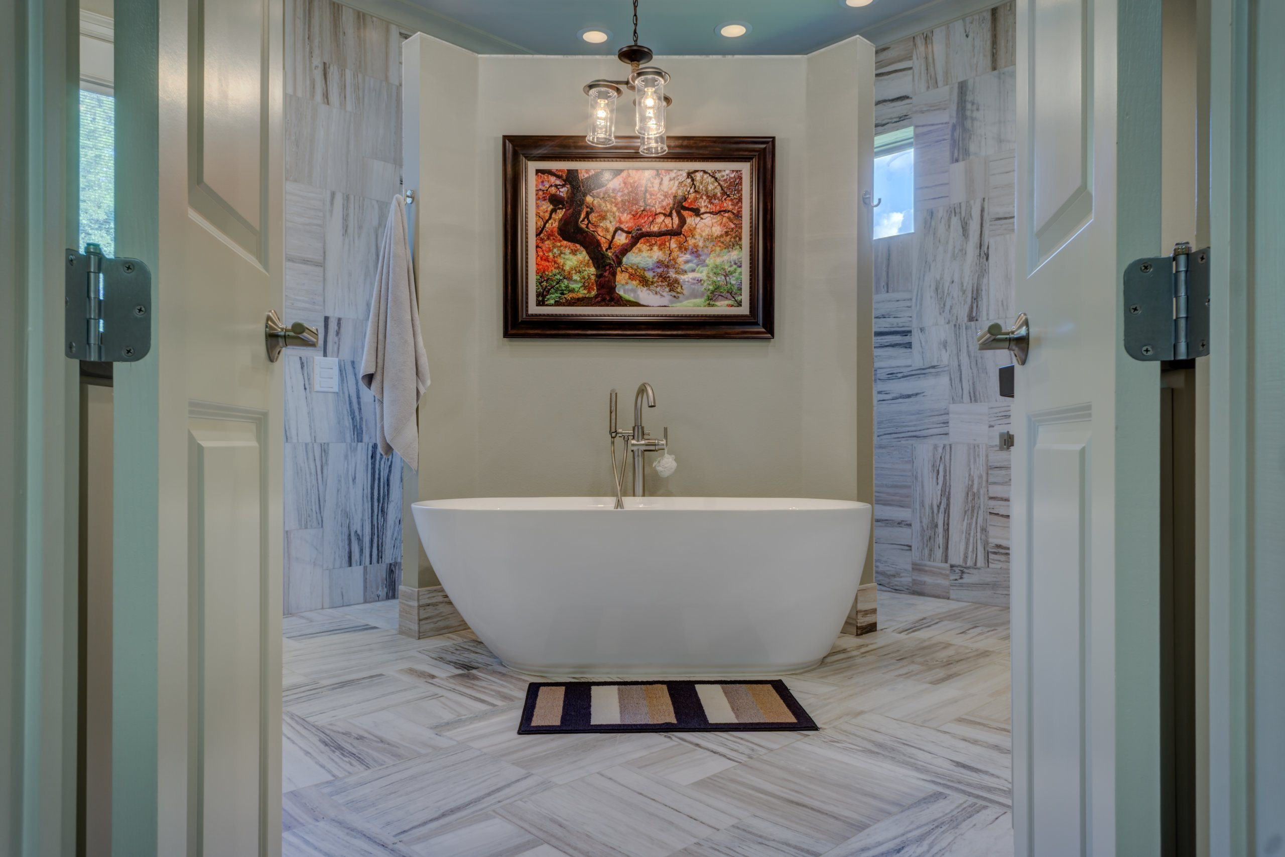 Colorful tree painting on top of white bath tub