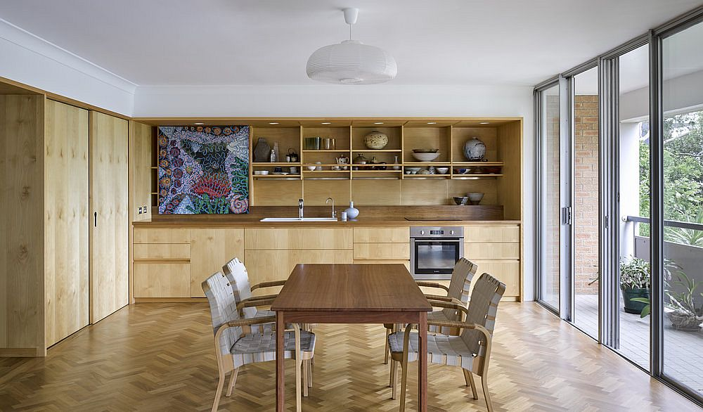 Curated and well-lit dining room and kitchen of the renovated home in Brisbane with a wood and white color palette
