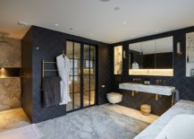 Dark-finishes-and-brass-fixtures-stand-in-contrast-to-the-polished-marble-surfaces-in-the-bathroom-56070-217x155